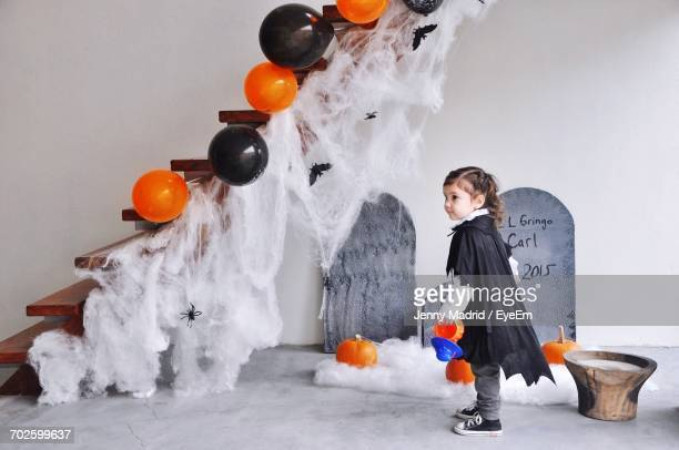 Full Length Of Girl Wearing Costume Standing At Decorated House During Halloween
