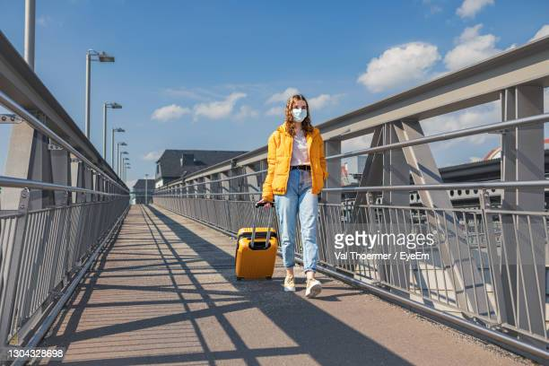 full length of girl wearing mask walking with suitcase against sky - val thoermer stock-fotos und bilder