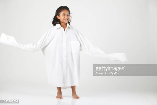 full length of girl wearing oversized shirt while standing against white background - surdimensionné photos et images de collection