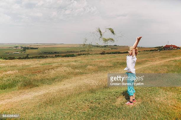 full length of girl with arms raised standing on grassy field against sky - bortes foto e immagini stock