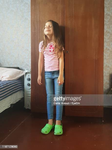 full length of girl with eyes closed standing against closet at home - elena knouzi stock pictures, royalty-free photos & images