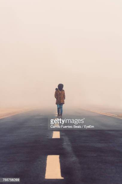 Full Length Of Girl With Hands In Pockets Standing On Road During Foggy Weather