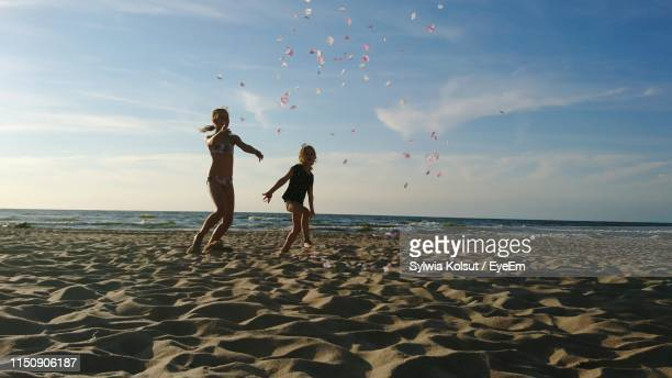 full length of girls playing at beach against sky - lazy poland stock photos and pictures