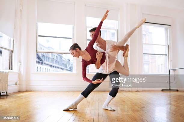 full length of graceful male and female ballet dancers performing in studio - picking up stock photos and pictures