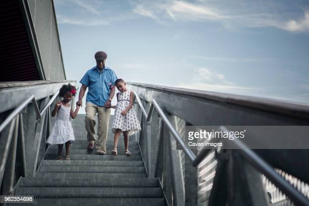 Full length of grandfather and grandchildren walking down steps against sky