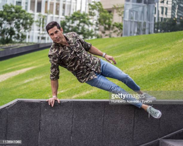 Full Length Of Handsome Mid Adult Man Balancing On Retaining Wall In Park