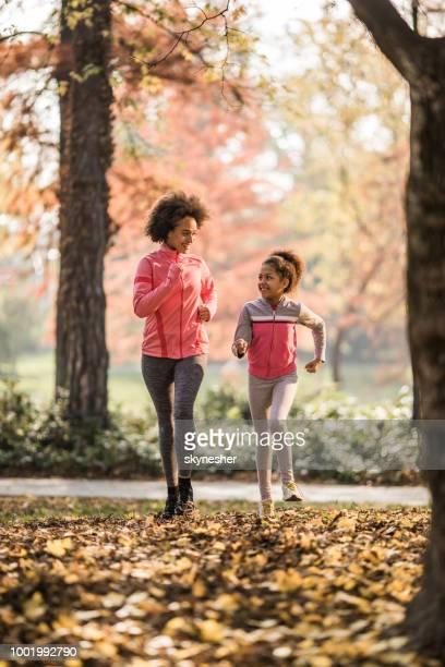 comprimento total da feliz mãe afro-americana e filha movimentando-se no outono. - vertical - fotografias e filmes do acervo