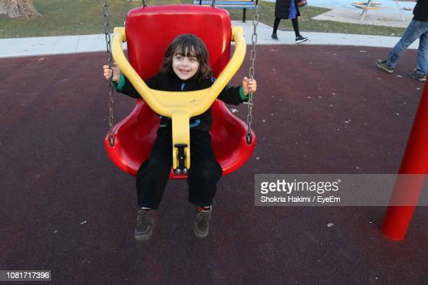 full length of happy boy on swing in playground - hakimi stock photos and pictures