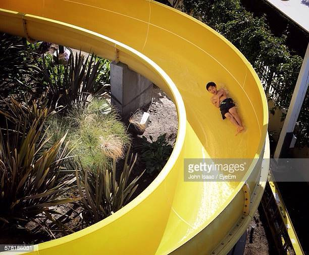 full length of happy boy on yellow water slide - sliding stock pictures, royalty-free photos & images