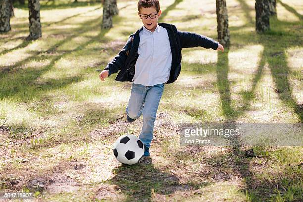 Full length of happy boy playing soccer in forest