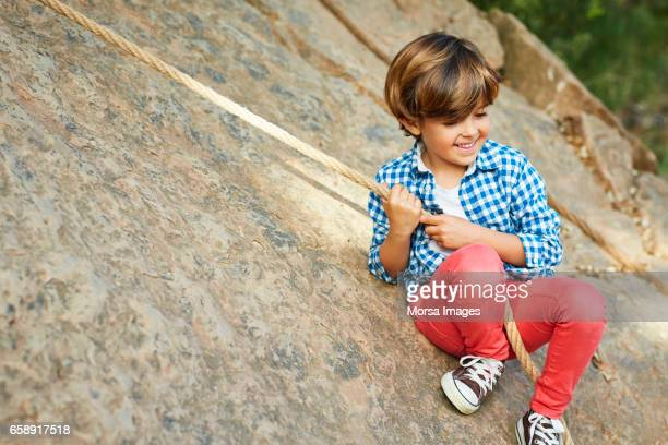full length of happy boy playing with rope on rock - red pants stock photos and pictures