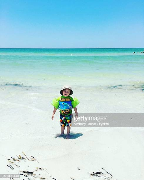 Full Length Of Happy Boy With Water Wings At Beach