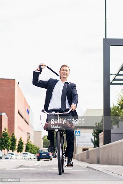 Full length of happy businessman removing tie while riding bicycle on city street