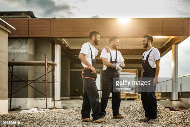 Gesamte Länge der glückliche Bauarbeiter auf einer Terrasse im Gespräch.
