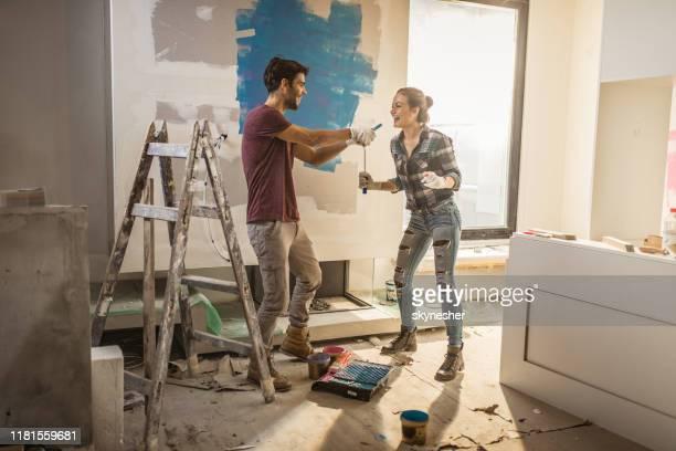 pleine longueur de couple heureux s'amusant tout en peignant leurs murs. - maison photos et images de collection