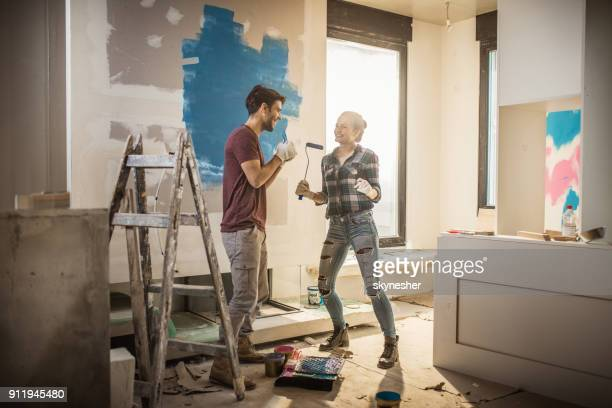 Full length of happy couple having fun while painting their walls.