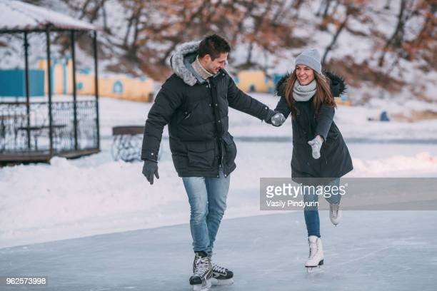 full length of happy couple holding hands while enjoying ice-skating - アイススケート ストックフォトと画像