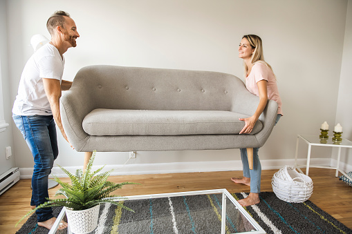 Full length of happy couple placing sofa in living room of new home 1070534588