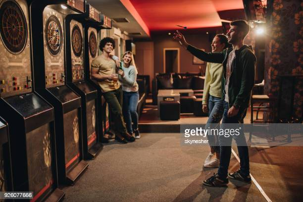 full length of happy couple playing darts in a bar. - darts stock pictures, royalty-free photos & images