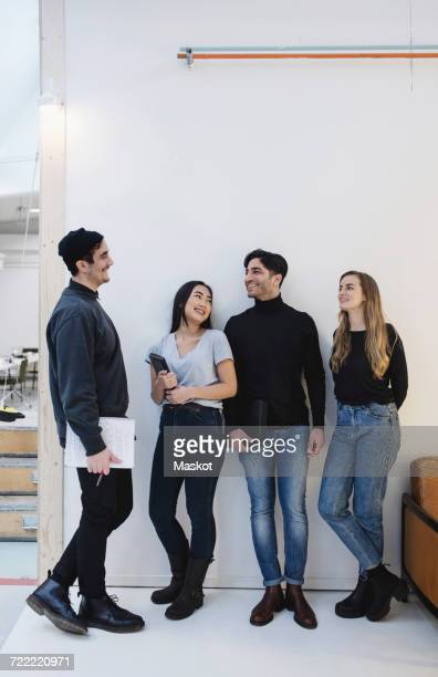 Full length of happy entrepreneurs talking while standing against white wall in office