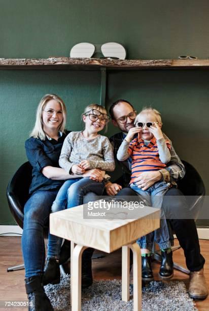 Full length of happy family at eyeglasses workshop