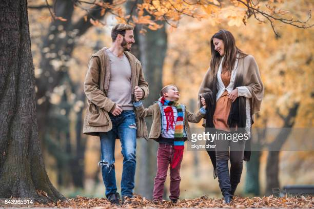 Full length of happy family communicating while taking a walk in autumn day.