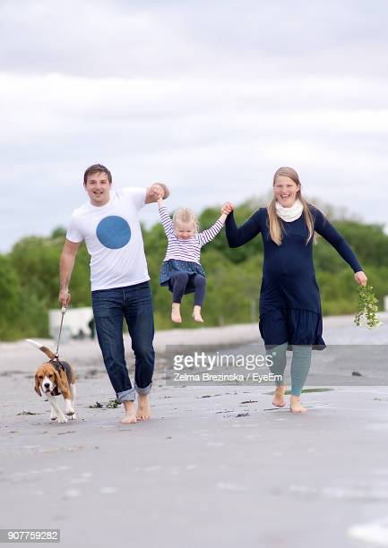 Full Length Of Happy Family Walking At Beach