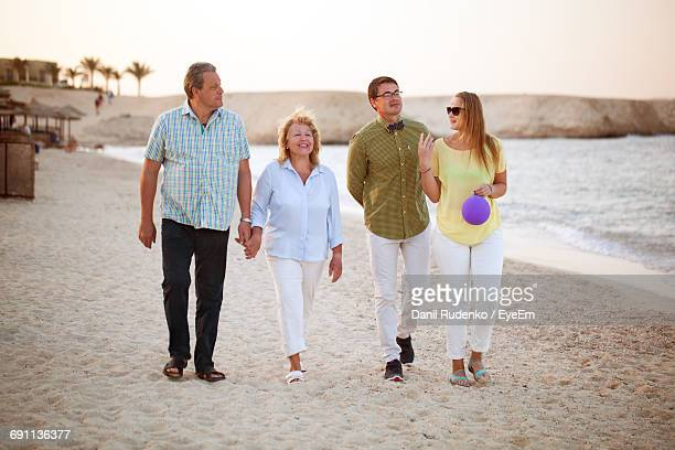 Full Length Of Happy Family Walking At Sandy Beach