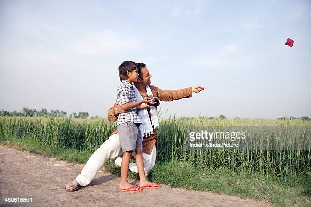 Full length of happy father and son flying a kite in field