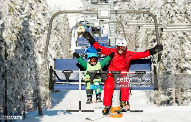 full length of happy father and son sitting on ski lift during winter - ski lift stock pictures, royalty-free photos & images