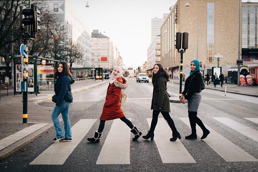 Full length of happy female friends crossing street in city - gettyimageskorea