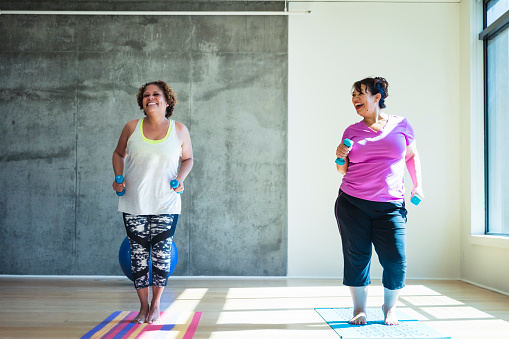 Full length of happy female friends using dumbbells while exercising against wall in yoga studio - gettyimageskorea
