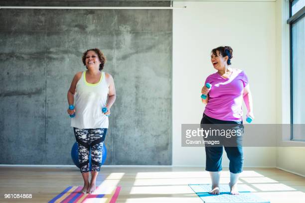 full length of happy female friends using dumbbells while exercising against wall in yoga studio - dikke vrouw stockfoto's en -beelden