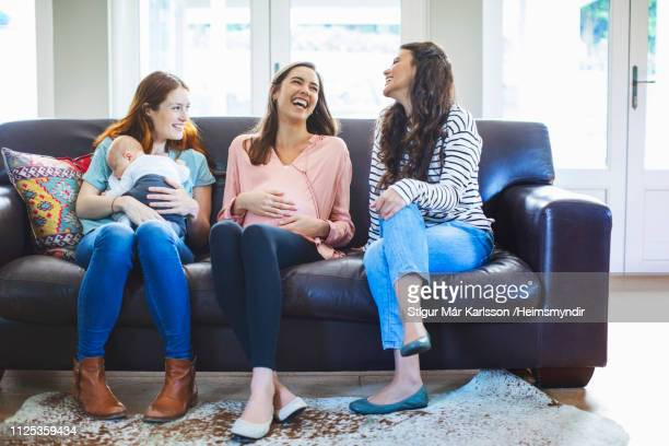 full length of happy female friends with baby boy - legs crossed at ankle stock pictures, royalty-free photos & images