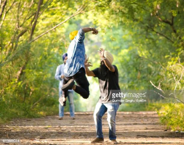 full length of happy friends on ground amidst trees - punjab india stock pictures, royalty-free photos & images