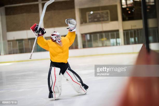 Full length of happy ice hockey goalkeeper celebrating his success at rink.