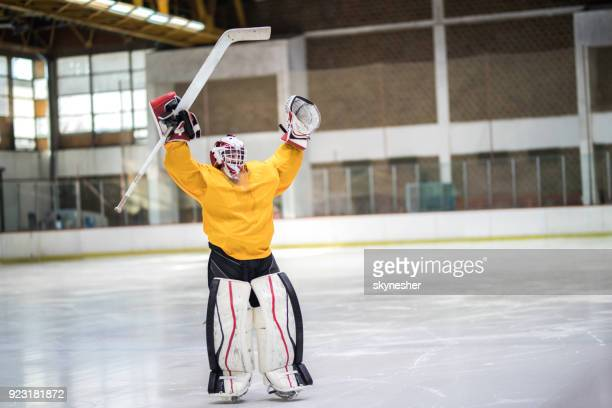 full length of happy ice hockey goalkeeper celebrating his success at rink. - ice hockey player stock pictures, royalty-free photos & images
