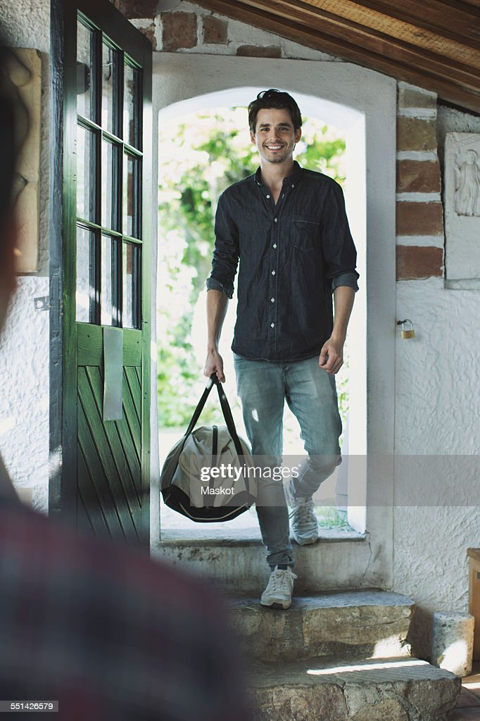 Full length of happy man welcomed by friends : Stock Photo