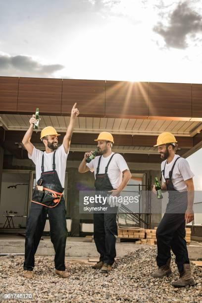 voller länge der glückliche arbeiter trinken bier auf baustelle. - feierabend stock-fotos und bilder