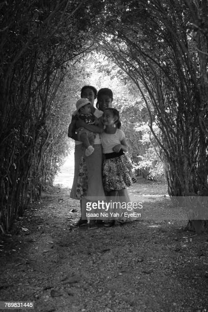 Full Length Of Happy Mother With Children Standing Amidst Trees
