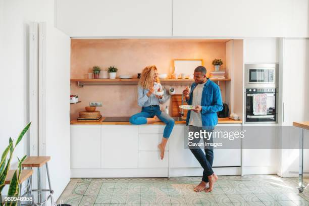 full length of happy multi-ethnic couple eating salad and sandwich in kitchen - standing photos et images de collection