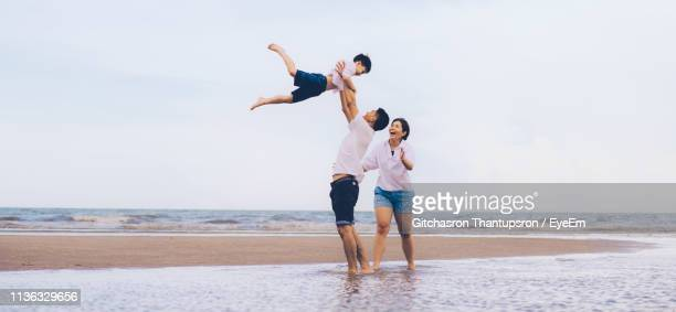 full length of happy playful family at beach against sky - mid adult women stock pictures, royalty-free photos & images
