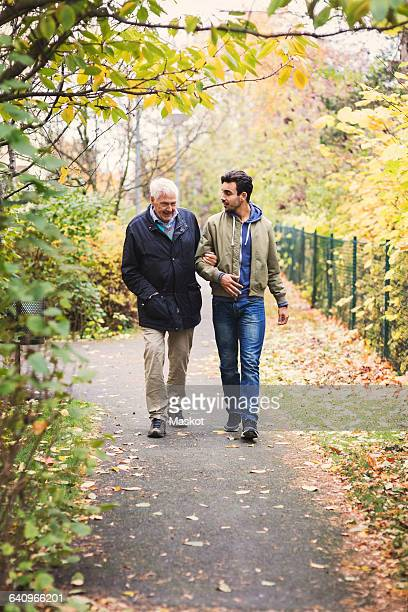 Full length of happy senior man with caretaker walking in park