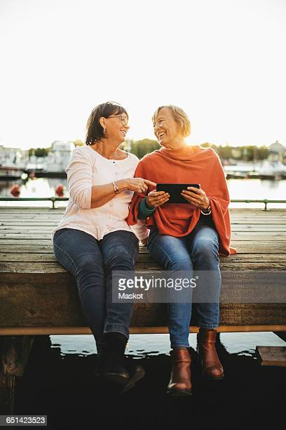 Full length of happy senior women using digital tablet on pier