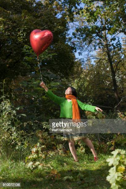 Full length of happy woman holding red heart shape balloon while standing at park
