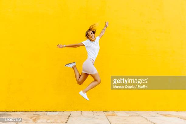 full length of happy woman jumping against yellow wall - 女性ダンサー ストックフォトと画像