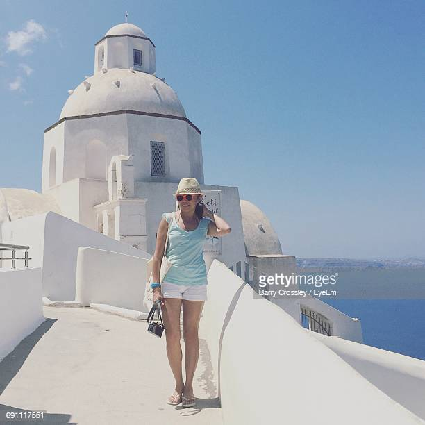 Full Length Of Happy Woman Standing Against Built Structure At Santorini