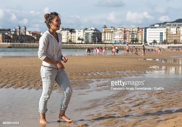 Full Length Of Happy Woman Standing At Sandy Beach In City