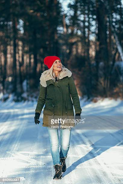 full length of happy woman walking on snow covered field - winter coat stock pictures, royalty-free photos & images
