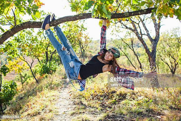 Full length of happy young woman climbing from branch in forest